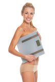 Smiling young woman in lingerie holding scales Stock Photography