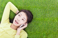 Smiling young woman listening with cell phone on grassland Royalty Free Stock Photos
