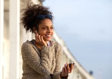Smiling young woman listening on headphones stock photos