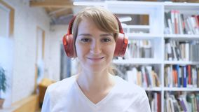 Smiling Young Woman Listening Music with Headphones royalty free stock image