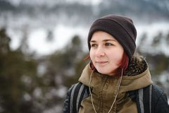 Smiling girl listening the music in winter mountains. Smiling young woman listening the music in winter mountains by white headphones royalty free stock image