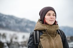 Smiling girl listening the music in winter mountains. Smiling young woman listening the music in winter mountains by white headphones stock image