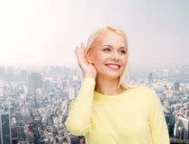 Smiling young woman listening to gossip Stock Photography