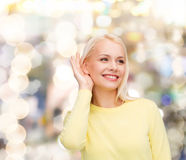Smiling young woman listening to gossip Stock Photos