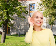Smiling young woman listening to gossip Stock Photo