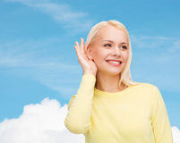 Smiling young woman listening to gossip Stock Image