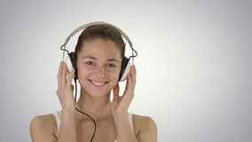 Smiling young woman listening to music with headphones on gradient background. royalty free stock photography