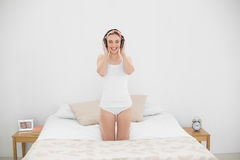 Smiling young woman listening to music in her bed Stock Images
