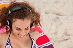 Smiling young woman listening to music with her headset. While sitting on her towel Stock Image