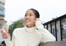 Smiling young woman listening to music on mobile phone Royalty Free Stock Photo