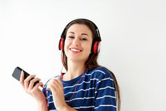 Smiling young woman listening to music with smart phone and headphones. Portrait of smiling young woman listening to music with smart phone and headphones Stock Photos