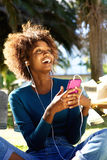 Smiling young woman listening to music with smart phone Stock Photo