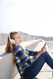 Smiling young woman listening to music with smart phone Royalty Free Stock Images