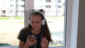 Smiling young woman listening to music. In front of a window on her mobile phone moving forwards and starting to dance and laugh stock footage
