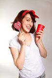 Smiling young woman with a lollipop and a cup posing  on Royalty Free Stock Images