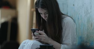 Smiling young woman with long dark hair reads something in her smartphone sitting on the floor in a room stock video footage