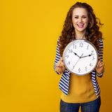 Smiling young woman against yellow background showing clock Royalty Free Stock Image