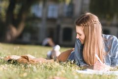 Young woman studying in park. Smiling young woman looking away while doing homework on grass in park Royalty Free Stock Photos