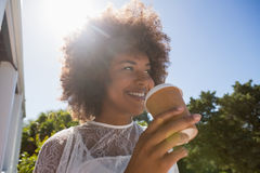 Smiling young woman looking away while holding disposable cup Stock Photography