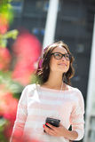 Smiling young woman looking away while listening music outdoors Stock Photo
