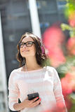 Smiling young woman looking away while listening music outdoors Stock Photography