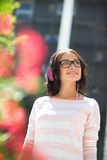Smiling young woman looking away while listening music on sunny day Stock Image
