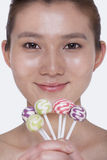 Smiling young woman looking into camera and holding up colorful lollipops, studio shot Stock Images