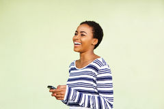 Smiling young woman looking at cell phone against green wall Royalty Free Stock Image