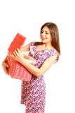 Smiling young woman looking in a laundry basket on white backgro Stock Image