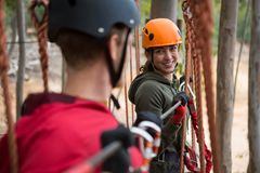 Smiling young woman looking at man while crossing zip line. In the forest royalty free stock photo