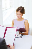 Smiling young woman looking at menu at restaurant Stock Image