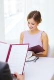 Smiling young woman looking at menu at restaurant Stock Image