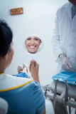 Smiling young woman looking at mirror Royalty Free Stock Image