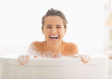 Smiling young woman looking out from bathtub Stock Image