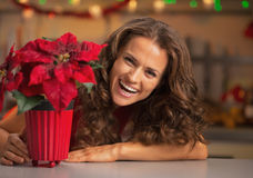 Smiling young woman looking out from christmas rose in kitchen Royalty Free Stock Photo