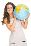 Smiling young woman looking out from earth globe Stock Image