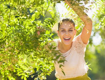 Smiling young woman looking out from foliage Royalty Free Stock Image