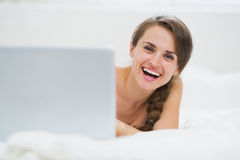 Smiling young woman looking out from laptop while laying in bed Stock Photography
