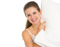 Smiling young woman looking out from pillow Stock Image
