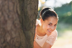 Smiling young woman looking out from tree Stock Images