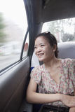 Smiling Young Woman Looking Out Window In Taxi, motion blur Royalty Free Stock Images