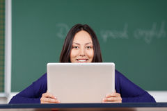 Smiling young woman looking over laptop at school Stock Photos