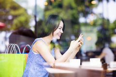 Smiling young woman looking at smart phone in cafe shop Royalty Free Stock Photos