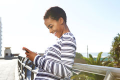 Smiling young woman looking at text on cell phone Royalty Free Stock Image