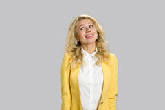 Smiling young woman looking upwards. Royalty Free Stock Photos