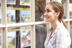 Smiling Young Woman Looking In Window Of Estate Agents Royalty Free Stock Photo