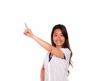 Smiling young woman looking at you and pointing up Stock Photos