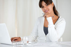 Smiling young woman looking at you using laptop. Portrait of a smiling young woman looking at you using her laptop at office - copyspace Stock Images