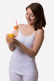 Smiling young woman looks at a glass of orange juice. Stock Photos