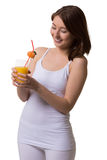 Smiling young woman looks at a glass of orange juice. Royalty Free Stock Images